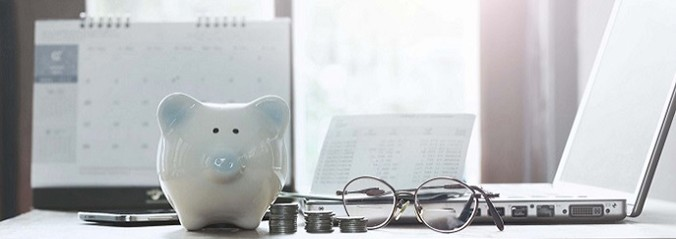 Close up image of a table with a laptop to the right, a pair of glasses and a white china piggybank in view with the sun shining in from the window in the background.