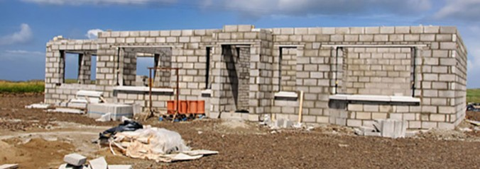 A house in the early stage of it's construction in a field with the outter walls built.