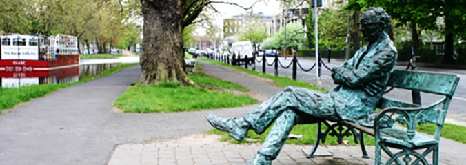 Statue of man sitting on bench with legs crossed by the Baggot Street Canal.