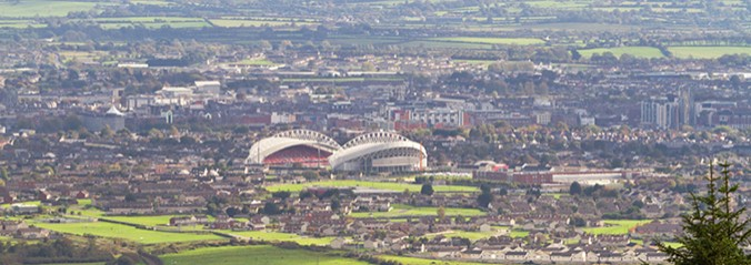 Picture of Thomnd Park stadium from afar with green fields in the forefront and the city in the background.