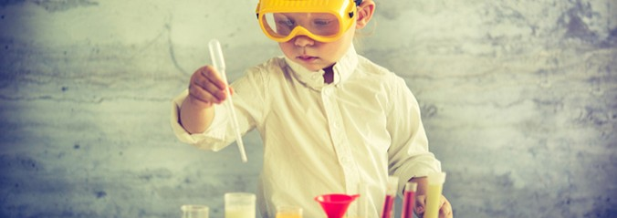 Picture of a little scientist at a table with yellow goggles.