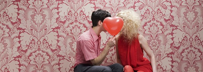 Man and woman sitting facing each other with a heart ballon being held up infront of their faces.