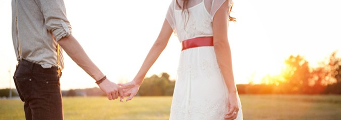Couple in a field holding hands at sunset.