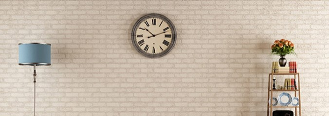 White brick wall with a rman numerial clock and a blue lampshade to the left with shelves to the right.
