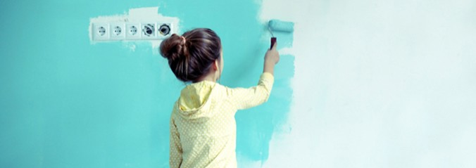 7 years old girl painting the wall at home turquoise.