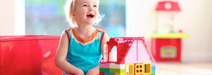 Lovely laughing little child, blonde girl of preschool age playing with colorful blocks sitting on a floor in a sunny room with a big window at home or kindergarten.