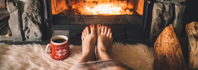 Point of view shot of a woman's feet in front of a fire with a cup of black coffee to the left.