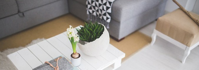 white coffee table with flower and vase. Grey sofa and beige chair in the backgound