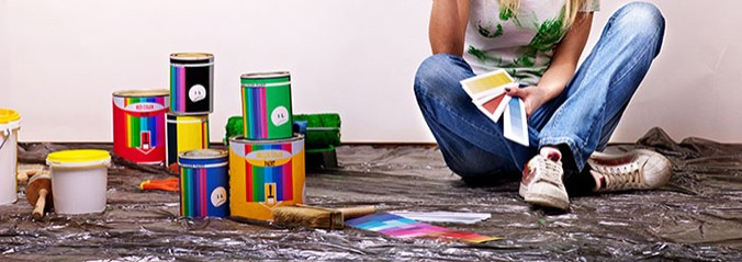 woman sitting beside tins of paint