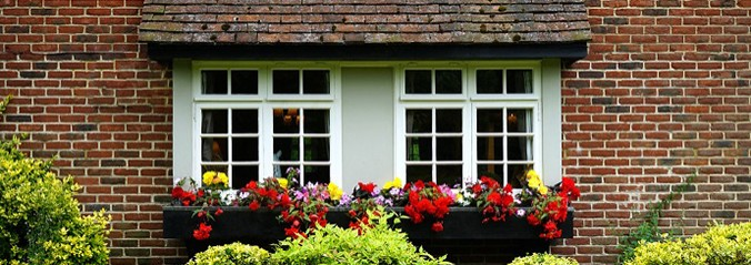 red brick house, white windows with flower boxes