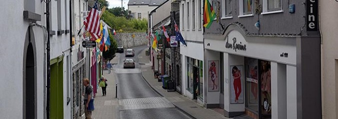Row of shops on street in Castlebar with flags outside