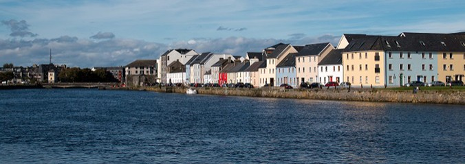 View of the River Corrib, Wolfe Tone bridge, and colorful houses in Galway Bay