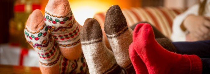 Closeup photo of family feet in wool socks at fireplace