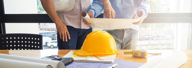 two men reviewing plans, yellow hard hat on table