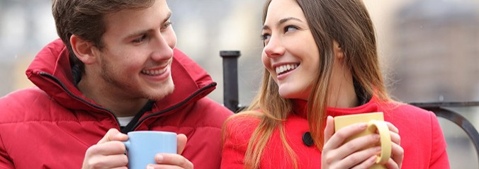 Couple talking relaxed sitting on a bench with coffee cups in winter