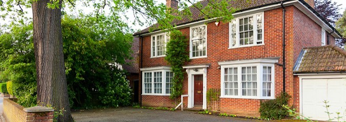 large red brick house with red door and tree in front garden