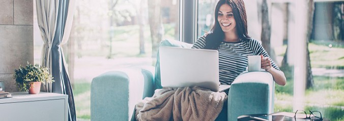 Smiling woman working on laptop and drinking coffee while sitting in a big comfortable chair at home